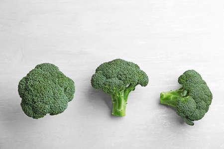 Fresh broccoli florets on light grey table, flat lay