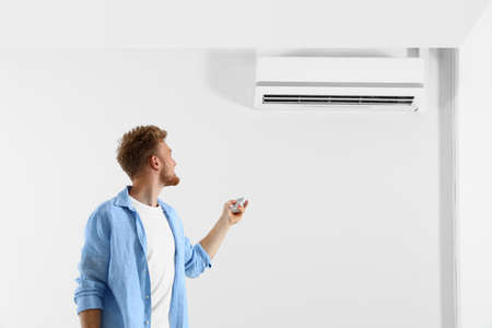 Young man operating air conditioner with remote control indoors. Space for text Stock Photo - 128827258
