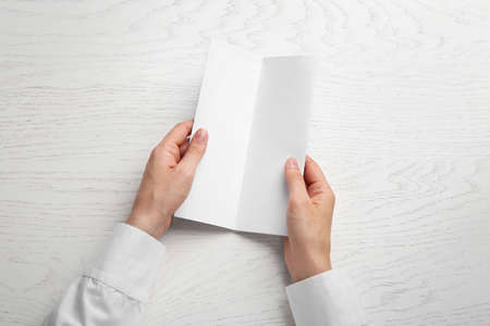 Young woman holding blank brochure at white wooden table, top view. Mock up for design 版權商用圖片