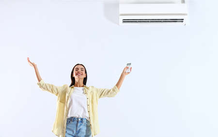 Young woman with air conditioner remote on white background