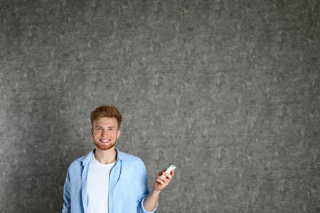 Young man with air conditioner remote on grey background. Space for text Stock Photo - 128827263