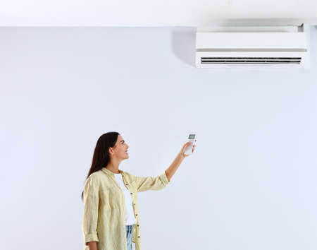 Young woman turning on air conditioner against white background Stock Photo - 128827282