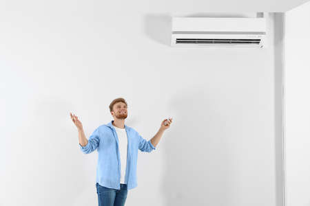 Young man operating air conditioner with remote control indoors. Space for text Stock Photo - 128827279