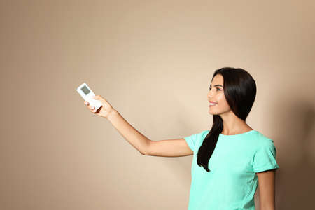Young woman with air conditioner remote on beige background. Space for text Stock Photo - 128827275