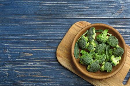 Bowl of fresh broccoli on blue wooden table, top view with space for text