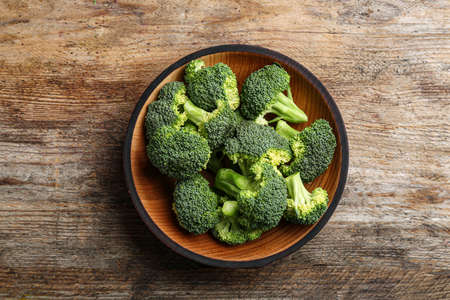 Wooden bowl of fresh broccoli on table, top view Imagens