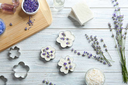 Flat lay composition of handmade soap bars with lavender flowers and ingredients on white wooden background Stock fotó