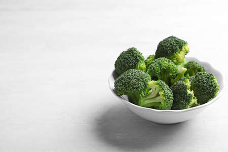 Bowl of fresh broccoli on light grey table, space for text Imagens