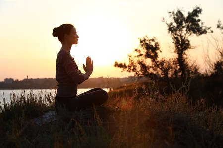 Young woman practicing yoga outdoors on sunset. Zen meditation 写真素材