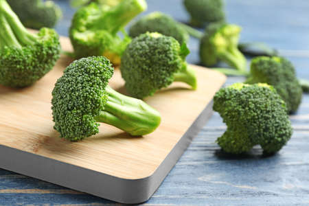 Board with fresh broccoli florets on blue wooden table, closeup Imagens