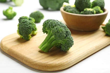 Composition with fresh broccoli on light table, closeup