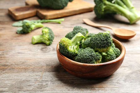 Bowl of fresh broccoli on wooden table. Space for text