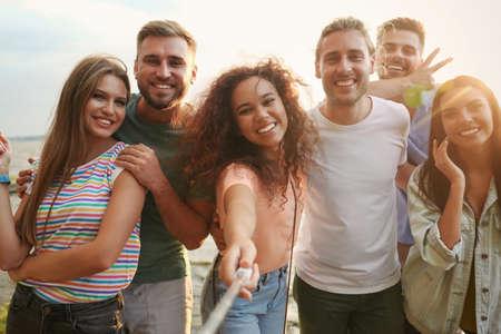 Szczęśliwi młodzi ludzie biorący selfie na zewnątrz w słoneczny dzień Zdjęcie Seryjne