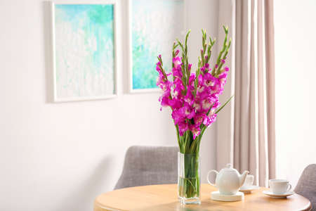 Vase with beautiful pink gladiolus flowers and tea set on wooden table in room, space for text