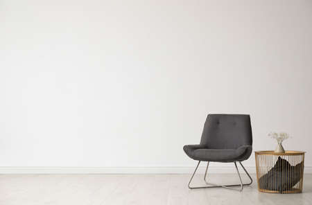 Stylowe wnętrze salonu z wygodnym krzesłem i stolikiem w pobliżu białej ściany. Miejsce na tekst
