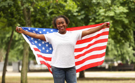Portrait of happy African-American woman with USA flag in park