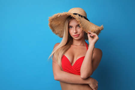 Pretty young woman wearing stylish bikini on blue background