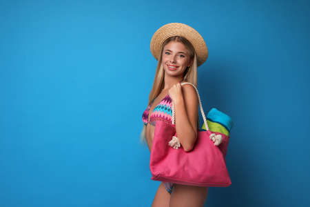 Pretty young woman wearing stylish bikini with bag on blue background. Space for text 写真素材