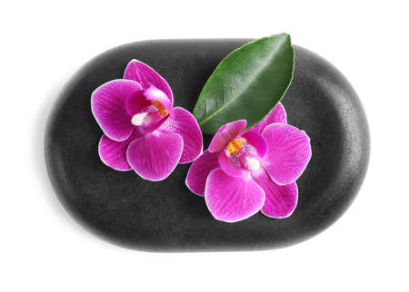 Spa stone and orchid flowers on white background, top view