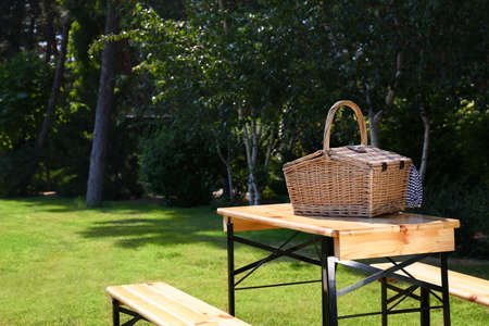 Picnic basket on wooden table in green park. Space for text