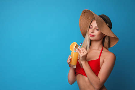 Pretty young woman wearing stylish bikini with cocktail on blue background. Space for text
