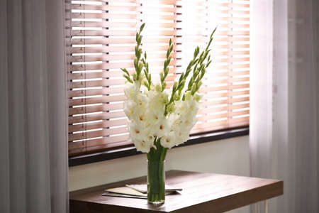 Vase with beautiful white gladiolus flowers on wooden table in room, space for text 스톡 콘텐츠