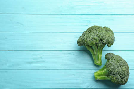 Flat lay composition of fresh green broccoli on blue wooden table, space for text 스톡 콘텐츠