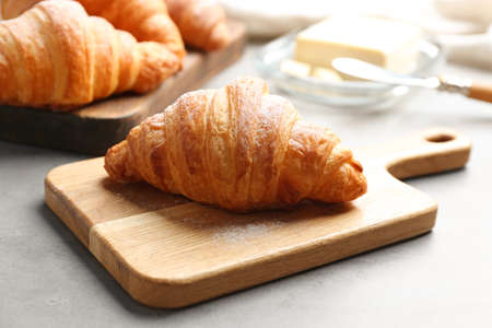 Wooden board with tasty croissant on grey table. French pastry 스톡 콘텐츠