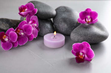 Spa stones, orchid flowers and candle on grey table