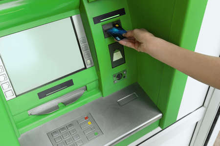 Mature woman using cash machine for money withdrawal, closeup