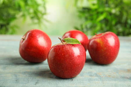 Ripe juicy red apples on blue wooden table against blurred background. Space for text 版權商用圖片