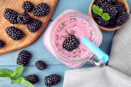 Flat lay composition with delicious blackberry smoothie on blue wooden background