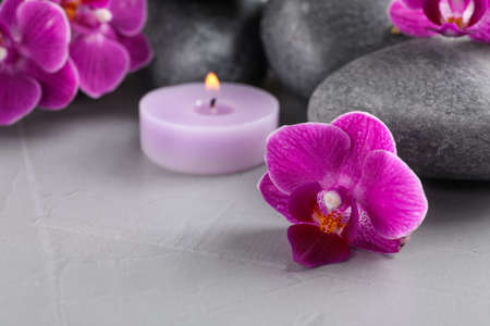 Spa stones, orchid flowers and candle on grey table, closeup