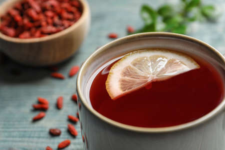 Healthy goji tea with lemon in cup on blue wooden table, closeup