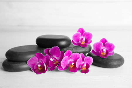 Spa stones and orchid flowers on white wooden table
