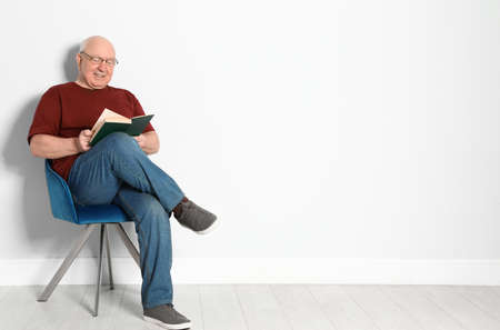 Portrait of senior man with glasses reading book near light wall. Space for text
