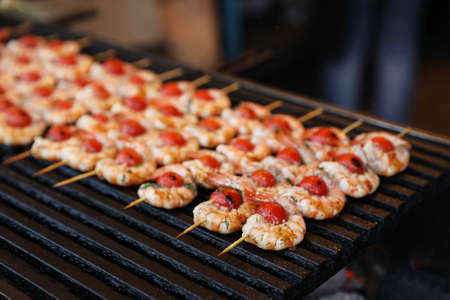 Delicious fresh shrimp skewers with cherry tomatoes on grill, closeup Stock Photo
