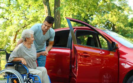 Joven ayudando a la mujer mayor discapacitada en silla de ruedas a entrar en el coche al aire libre Foto de archivo