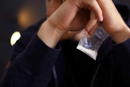 Criminal holding plastic bag with drug, closeup
