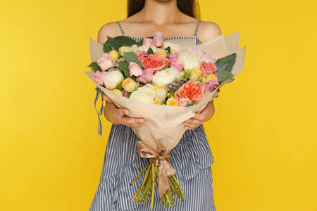 Young woman holding beautiful flower bouquet on yellow background, closeup