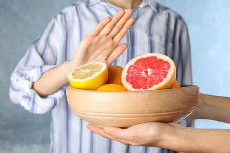 Woman refusing to eat citrus fruits, closeup. Food allergy concept