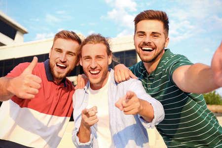 Hombres jóvenes felices tomando selfie al aire libre en un día soleado Foto de archivo