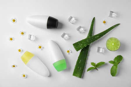 Composition with natural roll-on deodorants on white background, top view