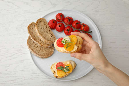 Woman eating delicious tomato bruschetta at white wooden table, top view
