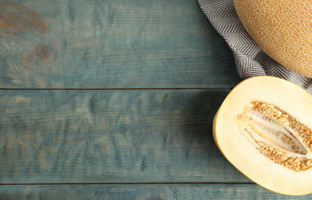 Tasty cut ripe melon on blue wooden table, flat lay. Space for text