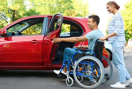 Young woman helping disabled man in wheelchair to get into car outdoors