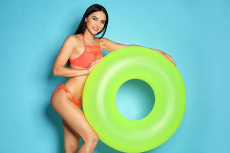 Beautiful young woman in stylish bikini with green inflatable ring on light blue background