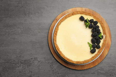 Delicious cheesecake decorated with blackberries on grey table, top view. Space for text 写真素材