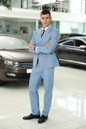 Młody sprzedawca w pobliżu nowego samochodu w nowoczesnym salonie Zdjęcie Seryjne