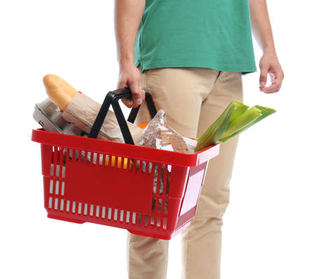 Young man with shopping basket full of products isolated on white, closeup